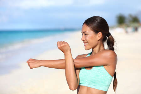 Athlete runner doing fitness warm-up before strength training stretching shoulder and arms. Sporty Asian woman preparing for workout and run doing body and arm muscle stretches happy on beach.