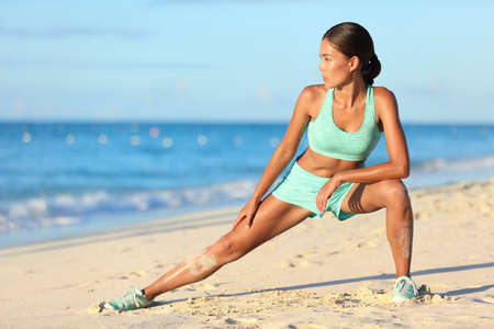 Runner woman stretching legs with lunge hamstring stretch exercise leg stretches. Fitness female athlete relaxing on beach doing a warm-up before her strength training cardio workout.