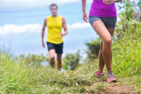 People running walking in nature on trail path. Group of runners hikers hiking in summer outdoors. Woman legs and man in the background. Fitness activity for a fit couple living a healthy lifestyle. 免版税图像