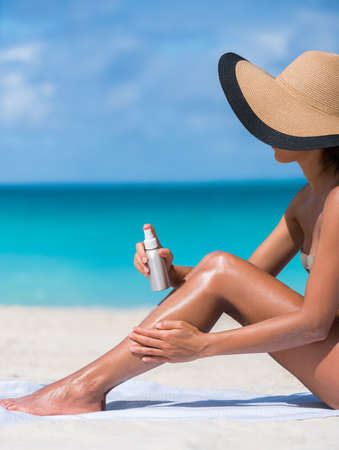 Sunscreen suntan lotion spray skincare product closeup of woman putting tanning oil on legs. Hand holding sunblock or mosquito repellent bottle spraying on body sunbathing at beach summer vacation. 免版税图像
