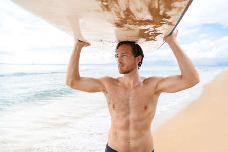 Handsome sexy active sporty topless man carrying his surfboard on the head. Surfer lifestyle on Hawaii beach during summer travel vacation. Caucasian athlete going out surfing with surf board.