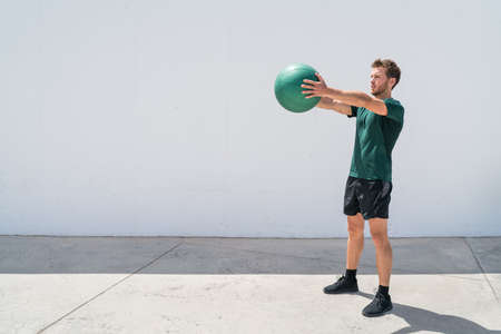 Medicine ball workout fitness man strength training arms doing deltoid front raise exercise for shoulder muscles. Upper body workout with weight ball at fitness centre. 免版税图像