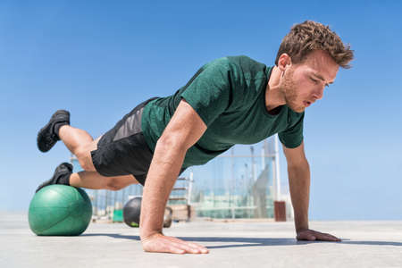 Man working out strength training doing incline push-ups workout at outdoor gym balancing on stability medicine ball with one leg raised. Bodyweight pushups exercises. Push-up variation. 免版税图像