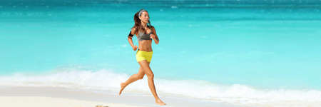 Healthy active lifestyle banner panorama. Fitness woman working out cardio running on beach wearing armband and earphones listening to phone music training jogging with blue background copy space. 免版税图像