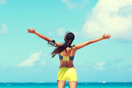 Fitness healthy lifestyle runner exercise success. Happy woman running with open arms in freedom listening to music with earphones and smartphone armband at beach ocean with sunshine filter. 免版税图像