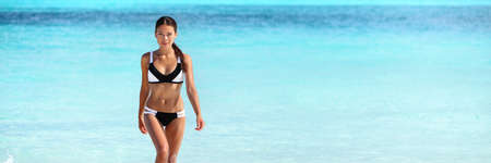 Asian bikini woman with slim body swimming in blue ocean banner of water copyspace. Travel holiday girl relaxing on beach vacation. 免版税图像