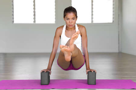 Yoga girl using blocks for jump through movement floating legs using abs muscles. Fitness woman training core during yoga practice at gym studio. 免版税图像