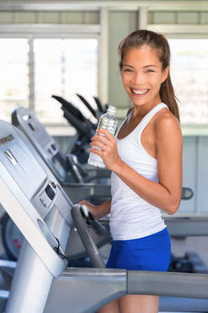 Runner woman drinking water in gym. Asian girl on running treadmill.