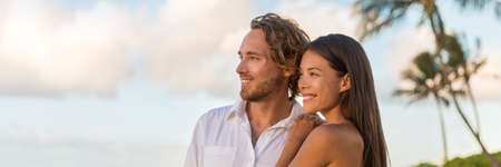 Relaxing multiracial couple watching sunset on beach vacation banner. Portrait of Asian woman, Caucasian man together enjoying looking at sky copy space. 免版税图像