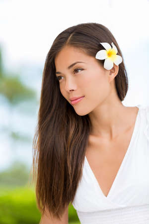 Asian mixed race beauty woman with healthy hair wearing hawaiian flower. Wellness skincare happy lifestyle. Serene multicultural girl outdoors at tropical spa. Young mixed race model on Hawaii. Banque d'images