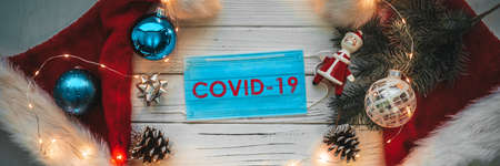 Christmas holidays during coronavirus outbreak. Panoramic banner of surgical mask for corona virus prevention top view with tree ornaments and santa hats.
