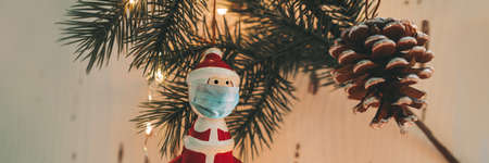 Christmas tree santa claus ornament wearing surgical face mask for coronavirus prevention during holiday family gathering. Banner of social distancing. 免版税图像