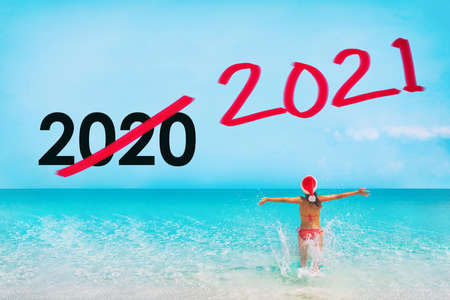 New Year 2021. 2020 coronavirus pandemic is over. Tourist with santa hat happy to be free to travel again to Caribbean beach. Text graphic design. 免版税图像