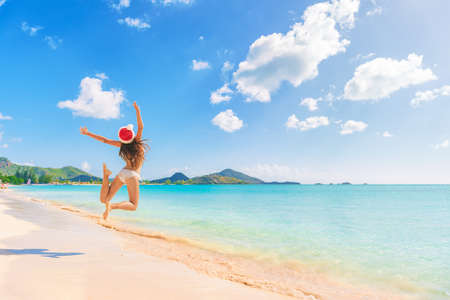 Christmas beach travel vacation santa hat happy woman jumping of happiness on Jolly Beach, Antigua, Caribbean island cruise destination.