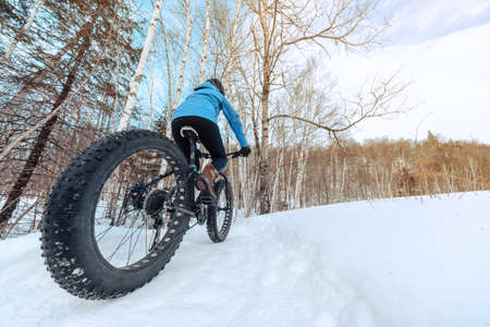 Fat bike biking girl riding on snow trail path in winter. Outdoor sport in nature landscape.