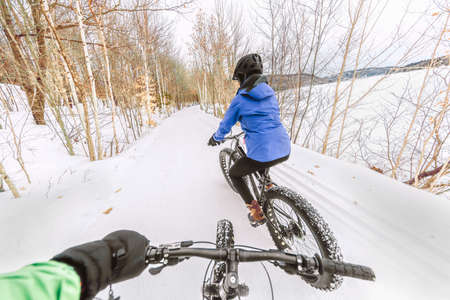 Couple biking on fat bikes on winter snow trail outdoor. Mountain nature landscape, woman rider cycling from behind with point of view of man holding handlebar of his bike.