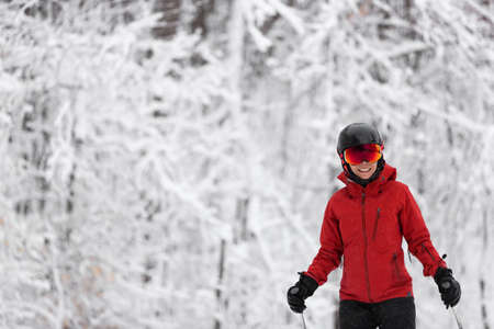 Winter sport happy skier Alpine skiing going dowhill against snow covered trees background during winter snowstorm. Woman in red jacket and goggles.
