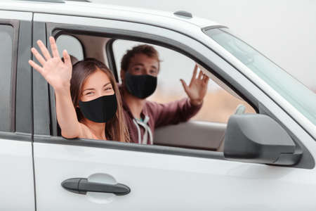 Happy driver and passenger waving hello driving new car on road trip or drivers license test at school. 免版税图像
