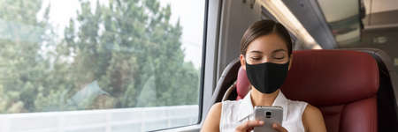 Train passenger Asian business woman using mobile phone during travel commute wearing face mask for corona virus pandemic. Panoramic banner of businesspeople commuting. 免版税图像