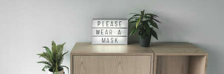 Please wear a mask business sign banner. Coronavirus prevention restriction notice at entrance. Mandatory facial covering wear inside store panoramic.