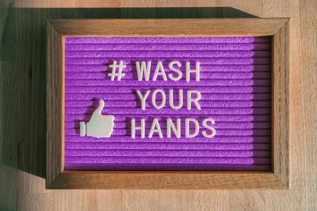 Wash your hands hashtag message on purple billboard notice at business store good hand hygiene for coronavirus prevention. Felt sign for social media against COVID-19. 免版税图像