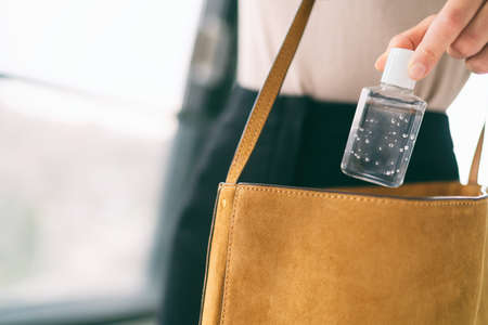 COVID-19 hand sanitizer woman using small sanitiser bottle in bag when going out walking to work in public, for washing hands disinfecting with alcohol gel dispenser.