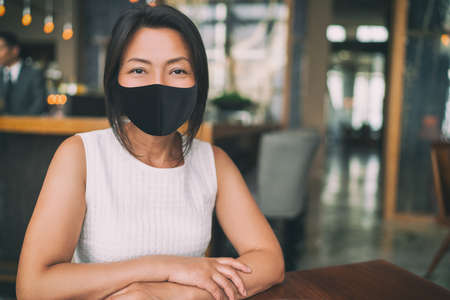 Asian mature business woman wearing protective face mask for coronavirus prevention in indoors public space as work office, restaurant, cafe.