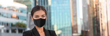 Woman wearing face mask at office work during coronavirus. Asian businesswoman portrait banner panoramic. 免版税图像