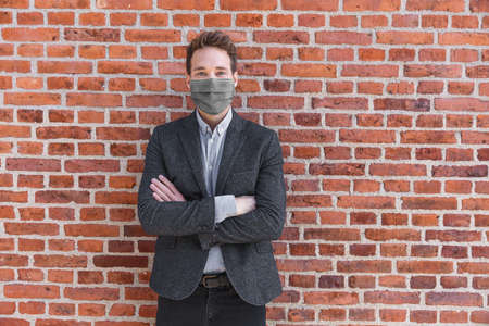 Man businessman confident portrait wearing face mask for coronavirus prevention in urban city brick background. Crossed arm entrepreneur or realtor.