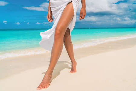 Elegant woman walking on Caribbean beach with slim smooth legs for skin care sun tan, wearing cover-up sarong wrap beachwear skirt relaxing on tropical travel holiday.
