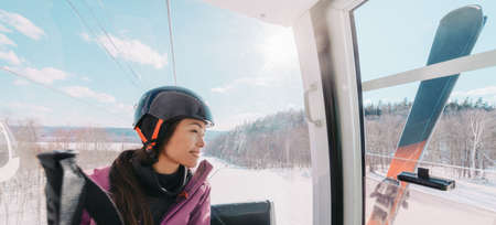 Winter sport Asian woman sitting in ski lift going up the hill at ski resort going skiing down the slopes. Banner panoramic of skier wearing helmet with skis. Stock Photo