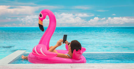 Relaxing woman floating in flamingo inflatable swimming pool toy at luxury resort using mobile phone sunbathing. Caribbean travel vacation hotel lifestyle.
