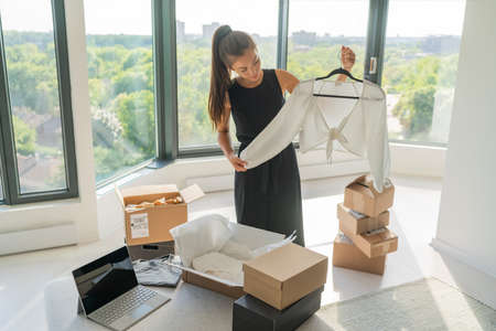 Selling clothing online using laptop at home woman packing new clothes in boxes to ship to customer. Asian girl happy looking at white long sleeve top folding it in box Stock Photo