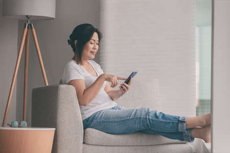 Work from home happy Asian mature woman relaxing in sofa using mobile phone online shopping or remote working Imagens