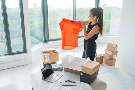 Selling clothing from home online store. Asian woman holding top putting in package next to laptop with black screen for ecommerce. Buying clothes opening shipping box