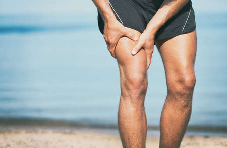 Sports injury muscle cramp pain fit runner man athlete holding painful thigh leg on outdoor summer jogging exercise. Fitness lifestyle