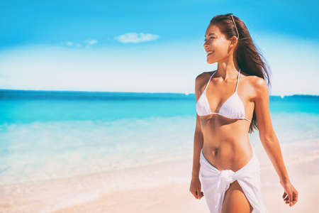 Bikini Asian woman in white swimsuit walking on ocean beach vacation for wellness spa luxury. Hair removal laser treatment summer ready body. Girl wearing pareo skirt beachwear.