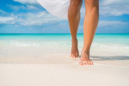 Elegant woman on luxury Caribbean beach vacation relaxing in summer tropical ocean background. Relax feet and legs walking enjoying sun tan lifestyle Standard-Bild