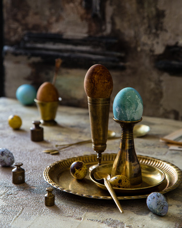 Easter eggs painted with natural dyes standing on brass golden stacks and plate on concrete background with branches with leaves