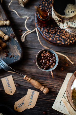 Vintage copper cups with coffee, coffee grains on wooden rustic table with strainer of cocoa powder, spoons, tags with word