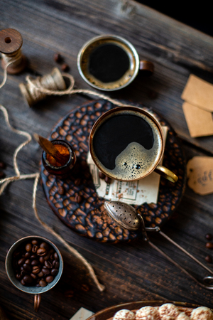 Vintage copper cups with coffee, coffee grains and dish with Tiramisu standing in the edge of shot on wooden rustic table with strainer of cocoa powder, boards. Overhead shot.