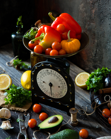 Assorted ripe vegetables on vintage black scales standing on rustic dark table with vegetables, herbs, scissors an metal basket with veggies 写真素材 - 121088616