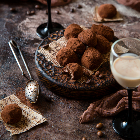 Homemade truffle candies standing on wooden board on beautiful brown concrete table with cocoa strainer, two wineglasses of liquor, brown cloth and coffee beans Stock Photo