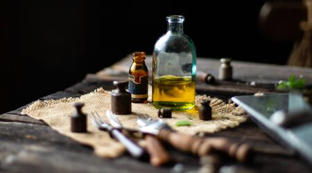 two vintage bottles with oil on sackcloth with old weights, forks on rustic wooden table, process of cooking, ingredients for cooking, selective focus, dark food photography