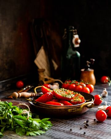 Homemade delicious cut in half tomatoes marinated with herbs, pepper, garlic on copper plates on wooden rustic table with old bottles, pepper mill, parsley, cherry tomatoes, forks. Selective focus 写真素材