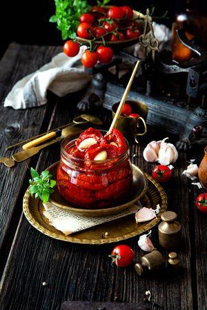 Tasty sun dried tomatoes with garlic, pepper, basil, olive oil in glass jar stands on brass plates on rustic wooden table with weights and old scales with cherry tomatoes