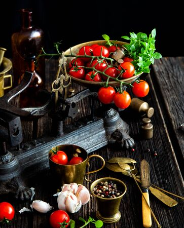 Tasty ripe cherry tomatoes with garlic, pepper, basil, olive oil on old scales on rustic wooden table with brass weights, spoons, knife 写真素材