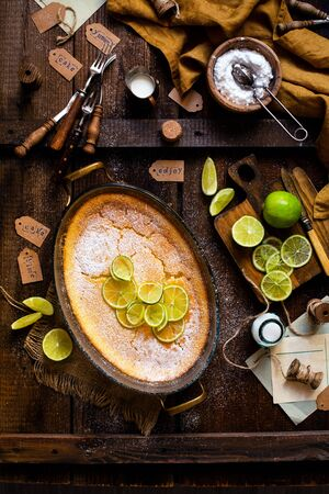 Overhead shot of homemade casserole, pudding, cheesecake, tart, pie or mousse with slices of lime in oval glass baking dish stands on rustic brown table with limes, forks, powdered sugar, strainer