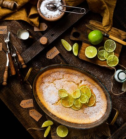 Overhead shot of homemade casserole, pudding, cheesecake, tart, pie or mousse with lime on top in oval glass baking dish stands on rustic wooden brown table with limes, forks, powdered sugar, strainer
