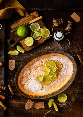Overhead shot of homemade casserole, pudding, cheesecake, tart, pie or mousse with slices of lime on top in oval glass baking dish stands on wooden brown table with limes, forks, bottle of sugar Reklamní fotografie